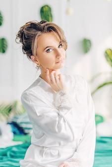 Piękna młoda panna młoda siedzi na łóżku pokrytym zielonym kocem w pokoju z kwiatami