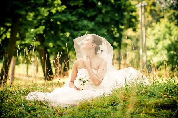 Piękna młoda panna młoda siedzi na zielonej łące w lesie