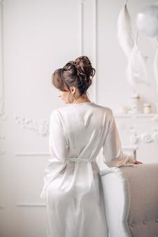 Piękna młoda panna młoda stojąca plecami do nas, oparta na szarym krześle z białym kominkiem