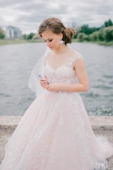Piękna młoda panna młoda w białym ślubnej sukni mieniu kwitnie przy naturą