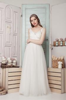 Piękna młoda panna młoda w ślubnej romantycznej dekoraci różowi i zielenieje. drewniane pudełka butelki i różne dekoracje ślubne