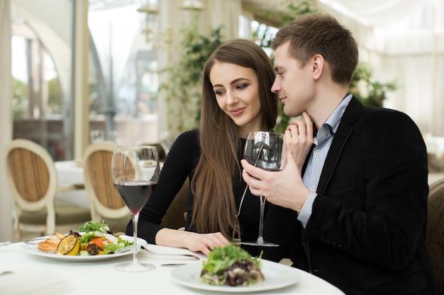 Piękna młoda para całuje w restauracji