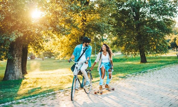 Piękna młoda para cieszy się na świeżym powietrzu i jeździ na rowerze w miejskim parku deskorolkowym