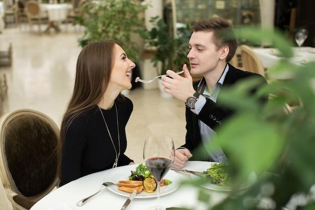 Piękna młoda para karmiąca się nawzajem i uśmiechnięta podczas spędzania czasu w restauracji