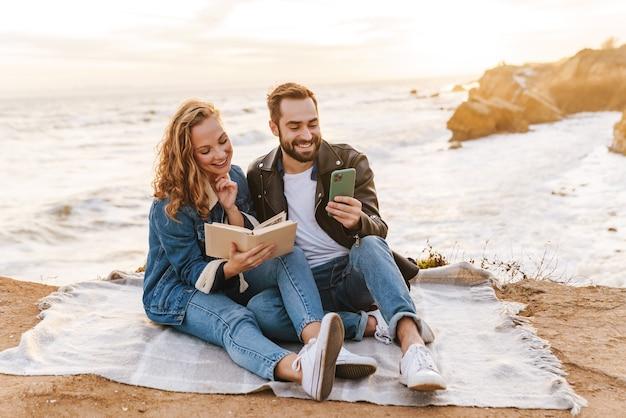 Piękna młoda para kaukaska pijąca kawę i korzystająca z telefonu komórkowego podczas spaceru nad morzem