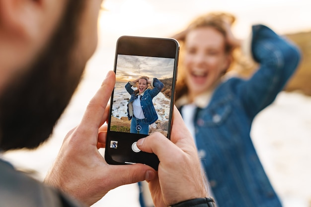 Piękna młoda para kaukaska robi zdjęcie na telefonie komórkowym podczas spaceru nad morzem
