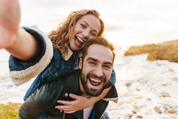 Piękna młoda para kaukaska uśmiechnięta i piggybacking podczas spaceru nad morzem