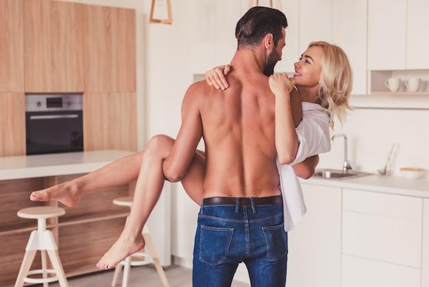 Piękna młoda para ma zabawę w kuchni w domu.