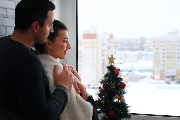 Piękna młoda para patrzy w dal przez okno owinięta ciepłym kocem i popijając herbatę