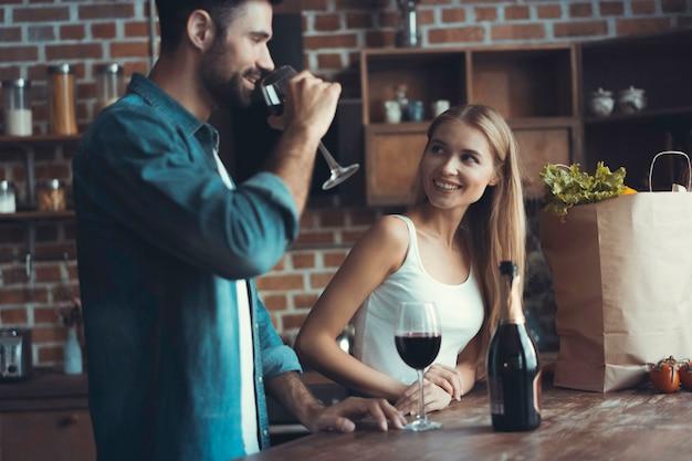 Piękna młoda para pije wino i uśmiecha się podczas gotowania w kuchni w domu.