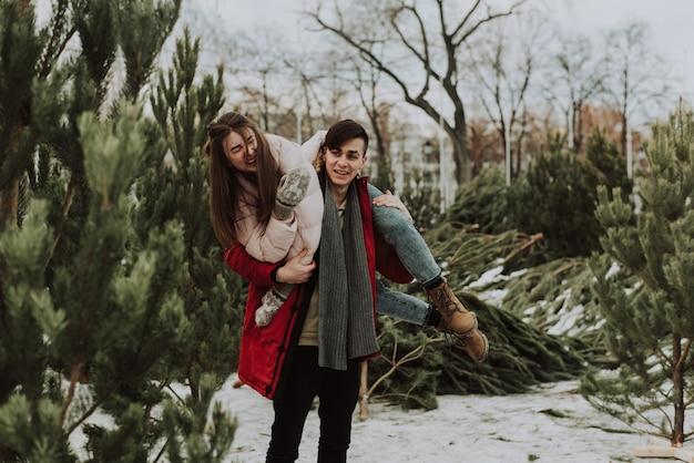 Piękna młoda para przyjechała wybrać drzewo. zakochani nowożeńcy wygłupiają się zimą. ładna kobieta śmieje się na ramionach mężczyzny.
