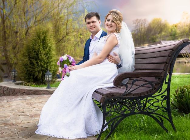 Piękna młoda para przytula się na ławce o zachodzie słońca