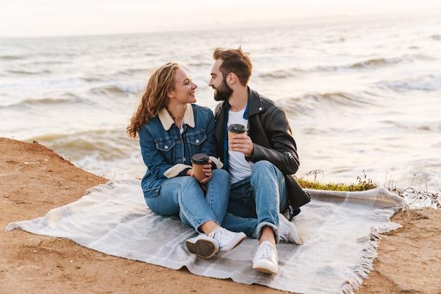 Piękna młoda para rasy kaukaskiej pijąca razem kawę podczas spaceru nad morzem