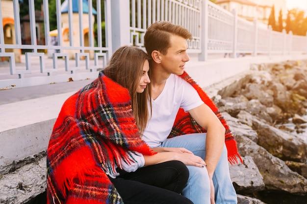 Piękna młoda para siedzi na kamiennym nasypie, zawinięta w koc