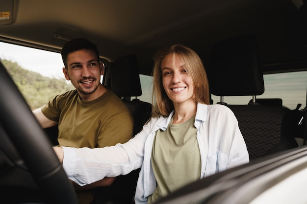 Piękna młoda para siedzi na przednich siedzeniach pasażera i prowadzi samochód