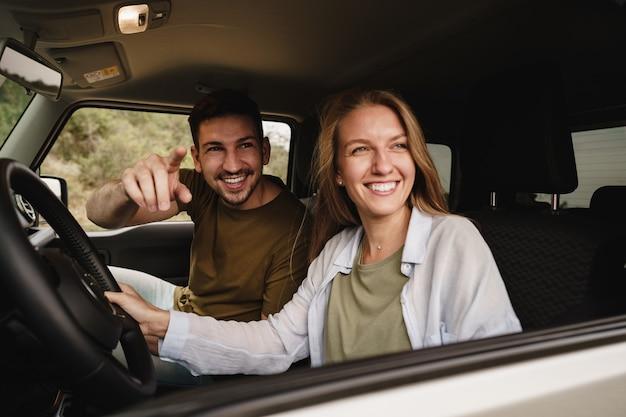 Piękna młoda para siedzi na przednim siedzeniu pasażera i prowadzi samochód