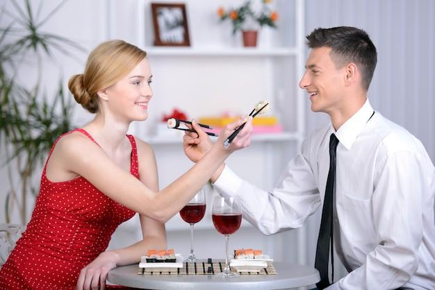 Piękna młoda para siedzi razem w restauracji.