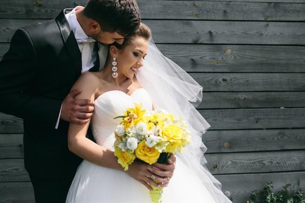 Piękna młoda para ślub stoi w pobliżu starego drewnianego domu