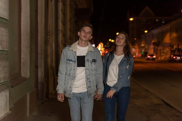 Piękna młoda para spaceru na ulicy. młoda para na romantyczną randkę wieczorem. miasto nocą w tle.
