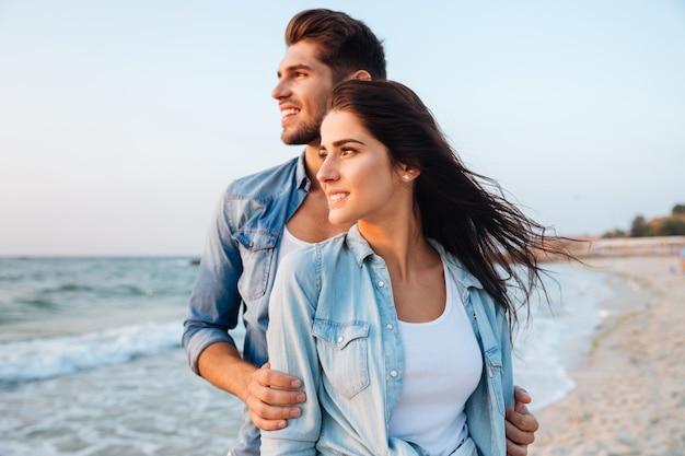 Piękna młoda para stoi i patrzy na fale na plaży