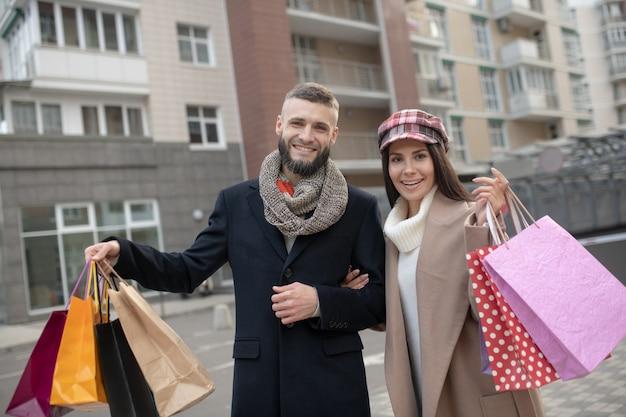 Piękna młoda para stoi z torby na zakupy, pokazując ci swoje zakupy