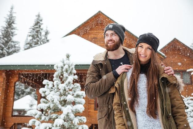 Piękna młoda para stojąca w pobliżu domku w śnieżnej pogodzie