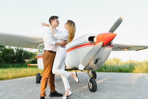 Piękna młoda para stylowe w oficjalne ubrania stojąc w prywatnym samolocie