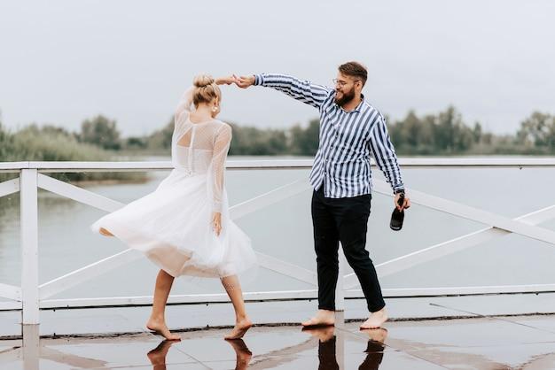 Piękna młoda para tańczy na bosaka i dobrze się bawi na molo nad wodą.