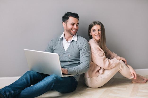 Piękna młoda para używa laptopa i uśmiecha się, siedząc na podłodze. zakupy online.