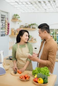 Piękna młoda para używa telefonu komórkowego i uśmiecha się podczas gotowania w kuchni w domu