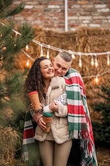 Piękna młoda para w białych ubraniach siedzi przy choince w ogrodzie. szczęśliwy mężczyzna i kobieta, romans, boże narodzenie, zabawa, miłość.