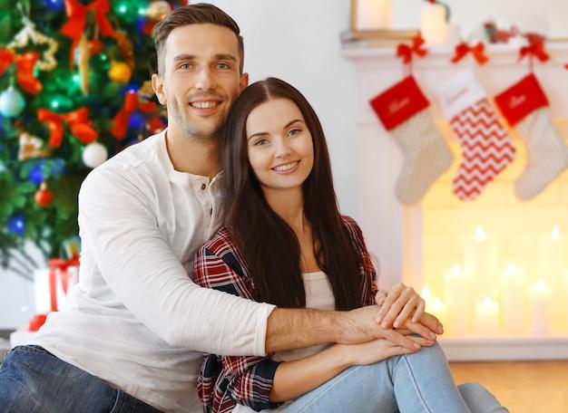 Piękna młoda para w salonie urządzonym na boże narodzenie