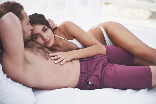 Piękna młoda para w strojach kąpielowych na plaży przed piaskiem uśmiech i przytulić.