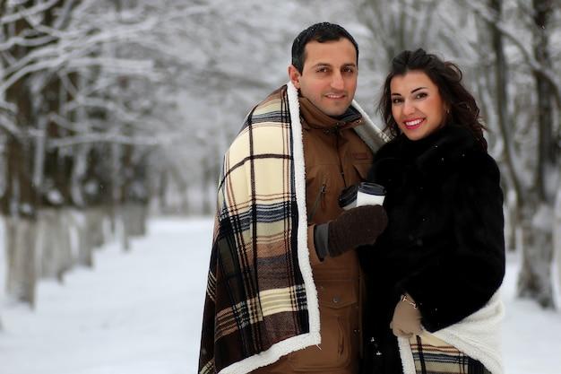 Piękna młoda para w zaśnieżonym parku owinięta w ciepłą kratę