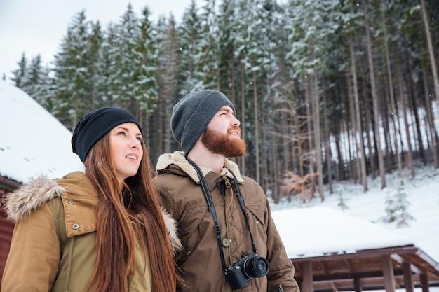 Piękna młoda para z aparatem fotograficznym stojąca i ciesząca się zimowym lasem