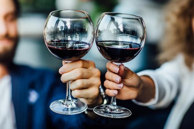 Piękna młoda para z kieliszkami czerwonego wina w luksusowej restauracji