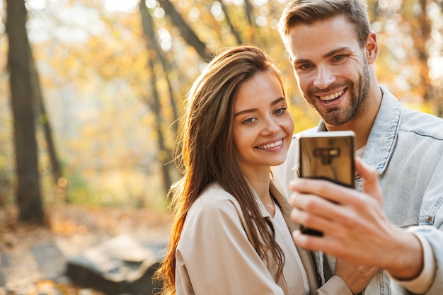 Piękna młoda para zakochana przy użyciu telefonu komórkowego podczas spędzania czasu w jesiennym parku, przy selfie