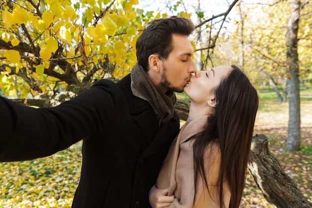 Piękna młoda para zakochana spędzająca razem czas w parku jesienią, robiąca selfie, całująca się