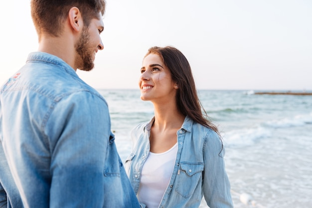 Piękna młoda para zakochana stojąca i patrząca na siebie na plaży