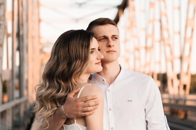 Piękna młoda para zakochanych, mężczyzna i kobieta, obejmują się, całują na dużym metalowym moście o zachodzie słońca.
