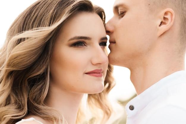 Piękna młoda para zakochanych, mężczyzna i kobieta obejmują się, całują w pobliżu błękitnego jeziora i piasku o zachodzie słońca.