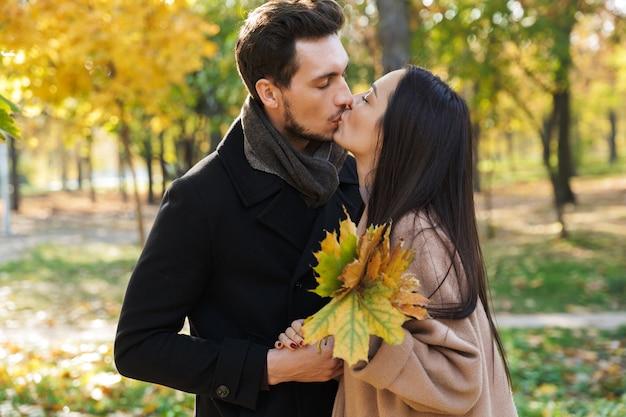 Piękna młoda para zakochanych spędzających razem czas w parku jesienią, całując