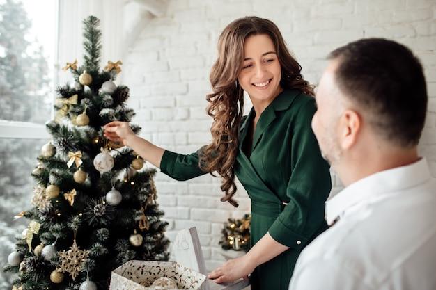 Piękna młoda para zakochanych zabawy podczas świętowania bożego narodzenia w domu, wspólne dekorowanie choinki.