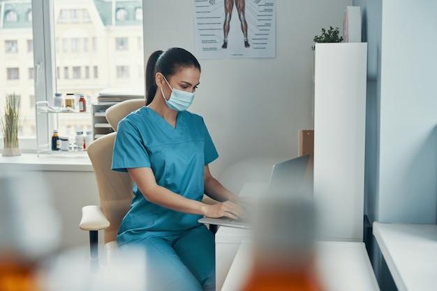 Piękna młoda pielęgniarka w masce ochronnej za pomocą laptopa siedząc w swoim biurze