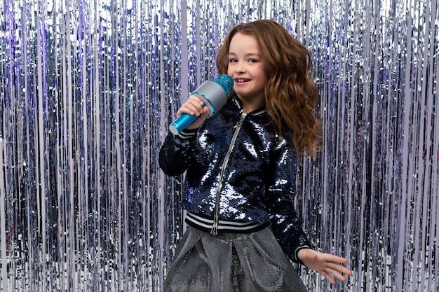 Piękna młoda piosenkarka rasy kaukaskiej z mikrofonem na ścianie blichtru