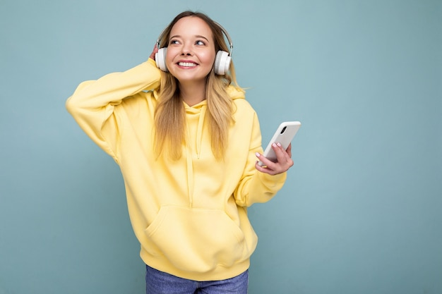 Piękna młoda pozytywna blondynka sobie żółtą stylową bluzę z kapturem na białym tle