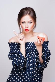 Piękna młoda retro pinup kobieta je słodkiego tortowego jedzenie