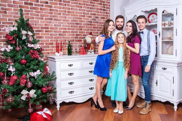 Piękna młoda rodzina ciesząca się świętami bożego narodzenia i przytulająca się z miłością