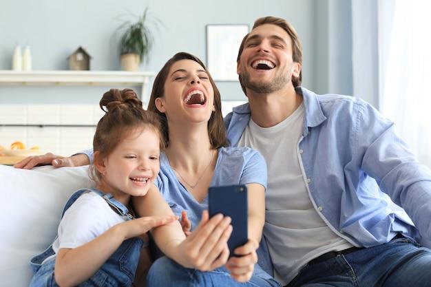 Piękna młoda rodzina z małym dzieckiem przy selfie ze smartfonem w domu na kanapie.