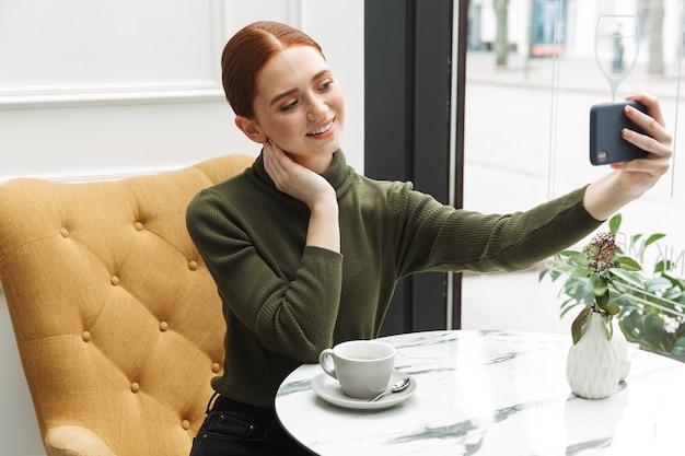 Piękna młoda ruda kobieta relaks przy stoliku kawiarni w pomieszczeniu, picie kawy, robienie selfie